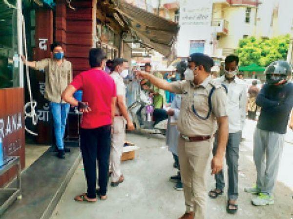 महम गेट चाैक पर दुकानदाराें काे लाॅकडाउन नियमाें की पालना करने बारे निर्देश देते डीएसपी वीरेंद्र सिंह। - Dainik Bhaskar