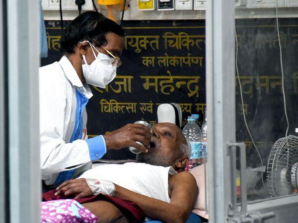 फोटो उत्तर प्रदेश की राजधानी स्थित राम मनोहर लोहिया अस्पताल की है। यहां एक कोरोना मरीज को पानी पिलाता हुआ स्वास्थ्यकर्मी। लखनऊ में पहले के मुकाबले अब कोरोना के नए मरीजों में गिरावट दर्ज हो रही है।