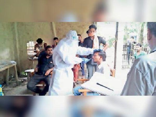 राघोपुर में कोरोना जांच के लिए सैंपल लेते स्वास्थ्यकर्मी। - Dainik Bhaskar
