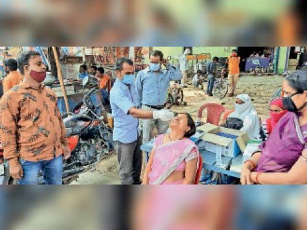 कोरोना जांच करते स्वास्थ्यकर्मी। - Dainik Bhaskar