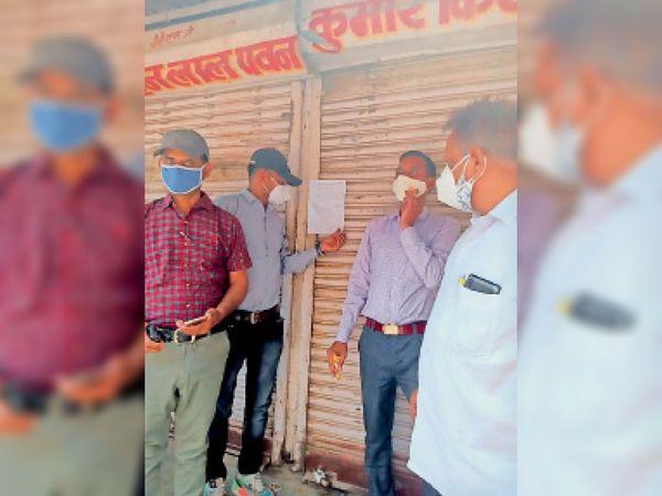 निर्धारित समय के उपरांत भी खुली मिली दुकान को सीज करते संयुक्त प्रवर्तन दल के अधिकारी। - Dainik Bhaskar