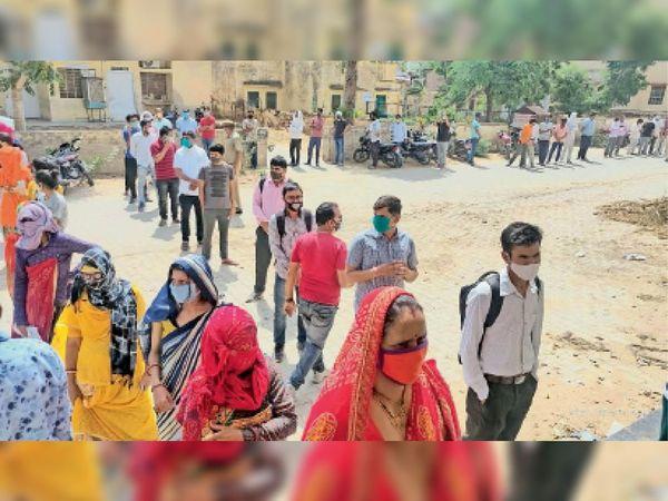 रींगस. सामुदायिक स्वास्थ्य केंद्र में टीकाकरण के लिए कतार में लगे महिला-पुरुष। - Dainik Bhaskar
