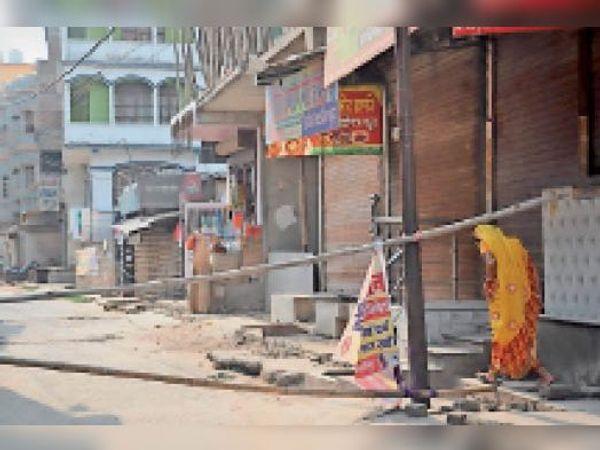 काशीपुर के एक गली में मौजूद कंटेनमेंट जोन से होकर गुजरती महिला। - Dainik Bhaskar