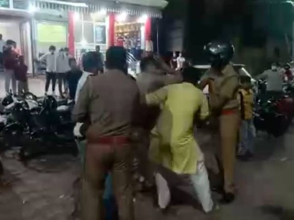 युवक को पीटते पुलिसकर्मी।