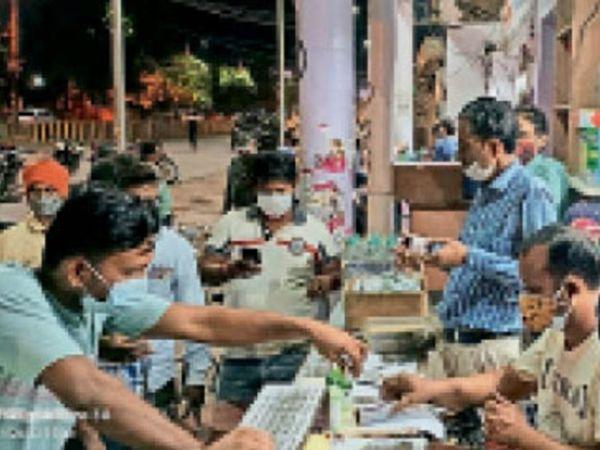 जिला अस्पताल के बाहर स्थित मेडिकल स्टोर पर दवाइयों के लिए कतार में खड़े लोग। - Dainik Bhaskar