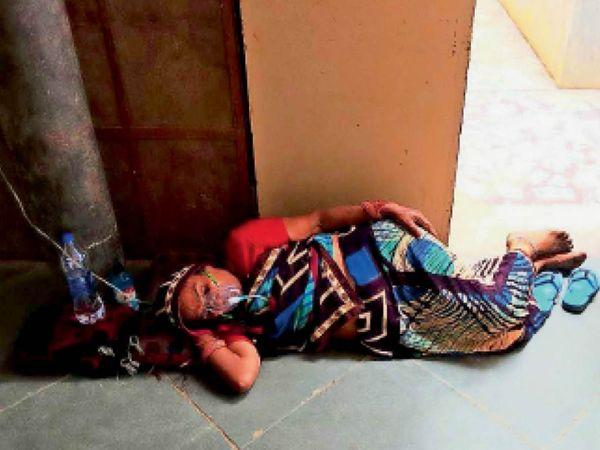 सांवली कोविड अस्पताल में बेड फुल हो गए हैंं। ऐसे में सोमवार को एक गंभीर महिला को ऑक्सीजन सिलेंडर के साथ नीचे ही लेटा दिया गया। - Dainik Bhaskar