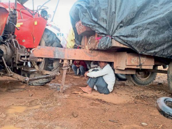 बारिश के कारण अपने को बचाने के लिए गालियों के नीचे बैठे किसान। - Dainik Bhaskar