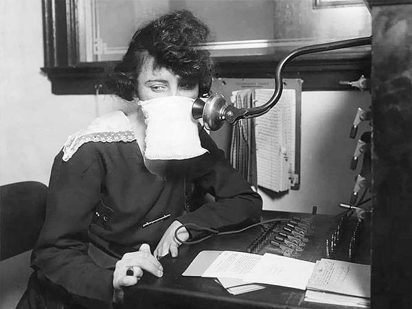 1918 की फोटो। टेलीफोन ऑपरेटर मास्क पहनकर बैठी हुई।