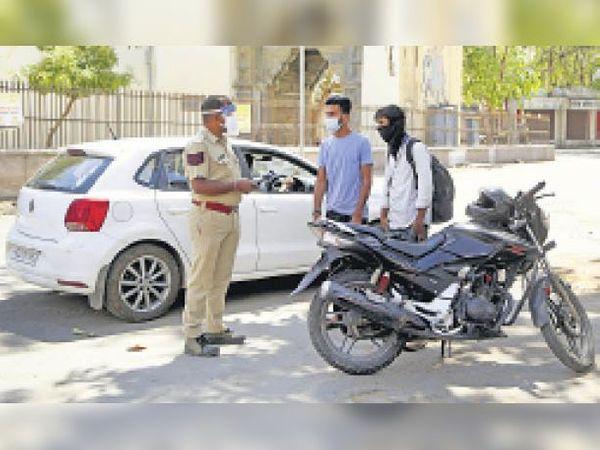 बेवजह सड़कों पर घूम रहे लोगों से पूछताछ करते हुए पुलिस जवान। - Dainik Bhaskar