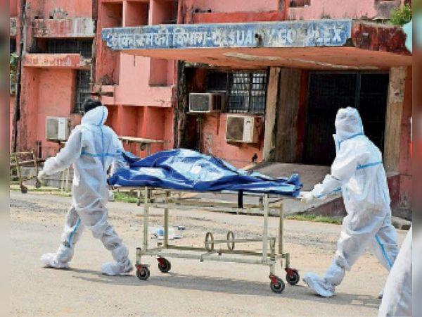 मायागंज में मौत के बाद काेराेना मरीज का शव ले जाते कर्मी। - Dainik Bhaskar