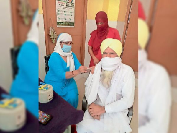 लाभार्थी को कोरोना से बचाव का टीका लगाती स्वास्थ्यकर्मी। - Dainik Bhaskar
