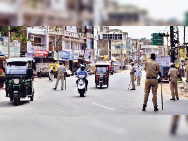 अलवर. मंगलवार सुबह काशीराम चौराहे पर बेवजह घूम रहे लोगों की निगरानी के लिए तैनात पुलिस। - Dainik Bhaskar