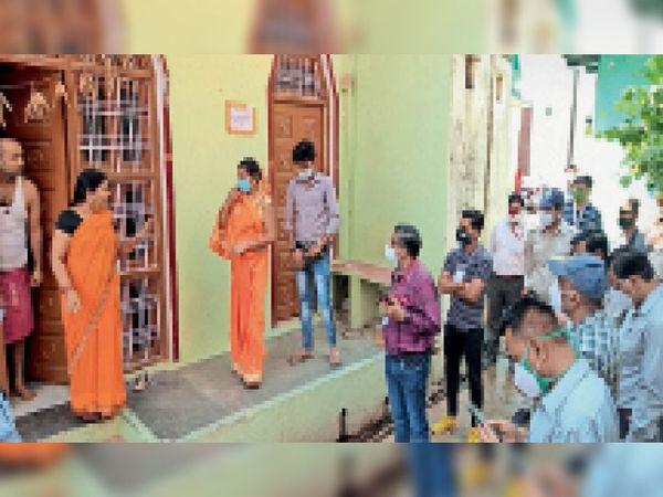 होलीपुरा में अपने घर के चबूतरे पर खड़ी स्वास्थ्य कार्यकर्ता अफसरों के सामने ही चेकअप कराने आए पति-पत्नी को डांटती हुई। - Dainik Bhaskar