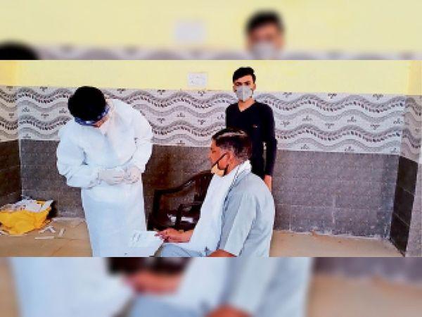 शहर में नगर पालिका के मैरिज गार्डन में बुजुर्ग का कोरोना सैंपल लेता स्वास्थ्य कर्मचारी। - Dainik Bhaskar