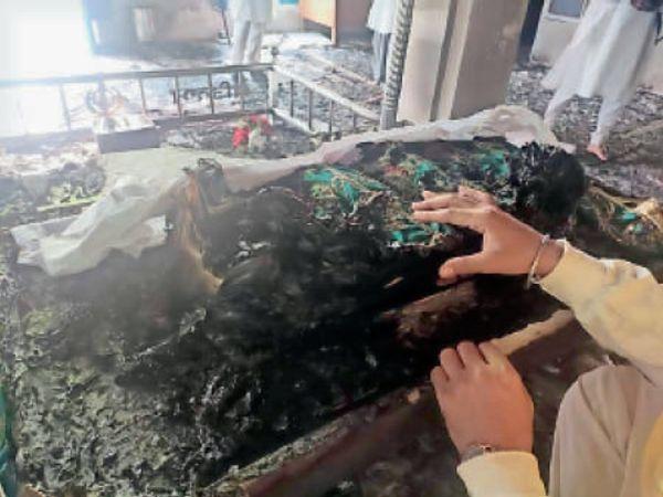 जले हुए गुरु ग्रंथ साहिब के पावर स्वरूप को संभालते गुरुद्वारे के सेवादार। - Dainik Bhaskar