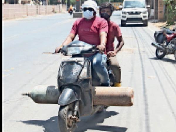 सांसों के लिए अस्पताल में जूझ रहे मरीजों के परिजन उनके लिए खुद ऑक्सीजन जुटाते हैं फिर दोपहिया वाहन से उसे अस्पताल तक पहुंचा रहे हैं। - Dainik Bhaskar