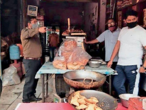 फोटो 2 मई की है। बाजार में दुकानदारों को कोविड नियमों की पालना के निर्देश देते एसडीएम गिरीश कुमार। - Dainik Bhaskar