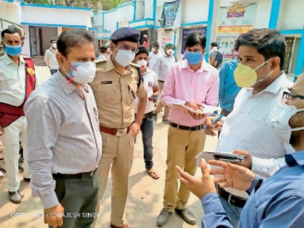 लॉकडाउन की तैयारियों को लेकर अधिकारियों से बातचीत करते डीएम। - Dainik Bhaskar