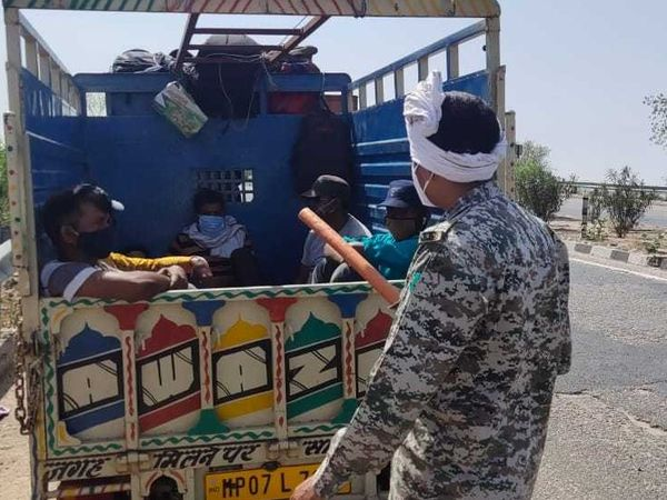 मंगलवार को धौलपुर से लोडिंग में छिपकर मुरैना आ रहे लोगों को रोकता पुलिसकर्मी। - Dainik Bhaskar