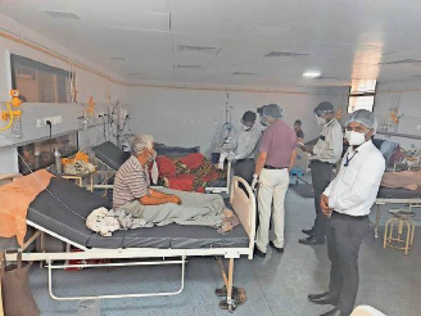 कोविड वार्ड के आईसीयू में भर्ती मरीजों से बातचीत करते डॉक्टर। - Dainik Bhaskar