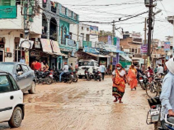 सड़क खराब होने के बाद कीचड़  के बीच से निकलती महिला। - Dainik Bhaskar