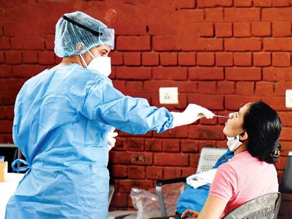 आईएसबीटी-17 में कोरोना जांच के लिए सैंपल देती एक महिला। - Dainik Bhaskar
