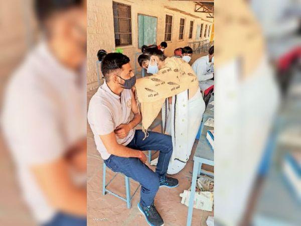 राधाबिहारी स्कूल में युवक के टीका लगाती नर्सिंग स्टाफ। - Dainik Bhaskar