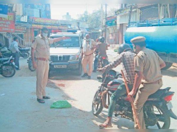 सिंघाना, बेवजह बाजार में घूमने पर बाइक को जब्त करते हुए पुलिस। - Dainik Bhaskar