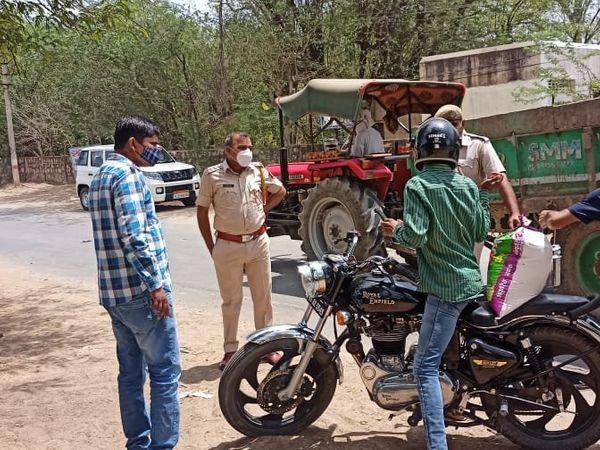 बाइक सवार से पूछताछ करती पुलिस - Dainik Bhaskar