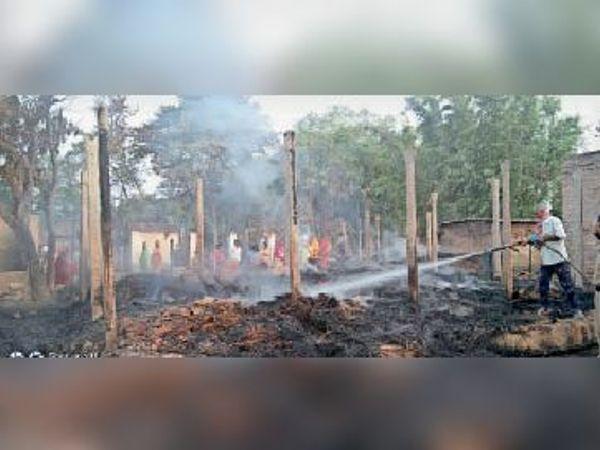 कमलदाहा गांव में लगी आग को बुझाते दमकल कर्मी। - Dainik Bhaskar