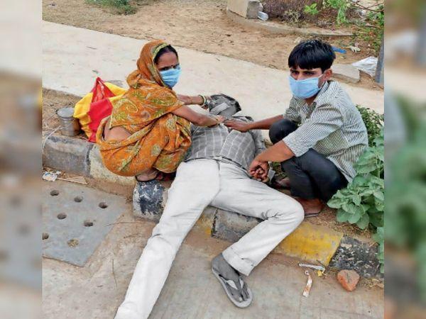 जेएएच स्थित सुपर स्पेशलिटी अस्पताल के बाहर पड़े प्रकाशचंद्र को ऑक्सीजन देती पत्नी और उसका बेटा। - Dainik Bhaskar