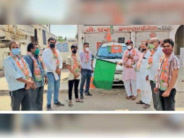 करौली| कोविड वायरस संक्रमण से आमजन के बचाव के लिए वेक्सीनेशन के प्रति जागरुक करने के लिए जागरुकता वाहन को हरी झंडी दिखाकर रवाना करते हुए भाजपा नेता। - Dainik Bhaskar