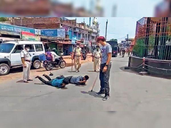 सड़क पर दो युवकों को लिटाकर सजा देते पुलिस के अफसर और कर्मी। - Dainik Bhaskar