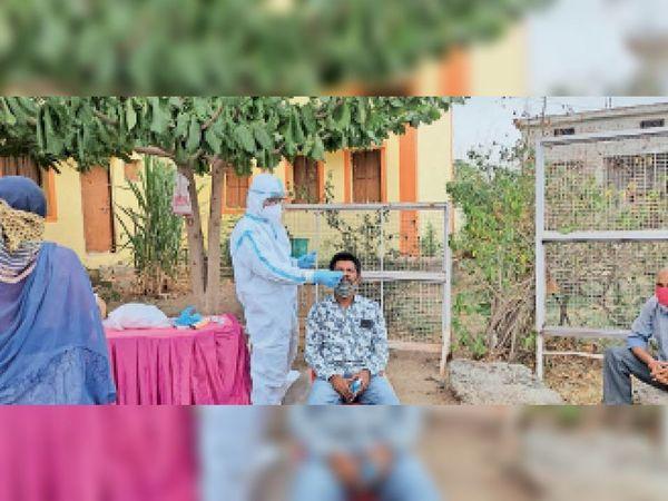 धरावरा काेविड केयर सेंटर पर मरीज के परिजन का सैंपल लेते स्वास्थ्य विभाग के कर्मचारी। - Dainik Bhaskar