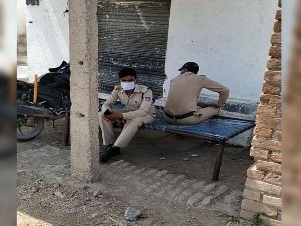 गांव के रास्ते पर तैनात पुलिस जवान पहरा दे रहे हैं