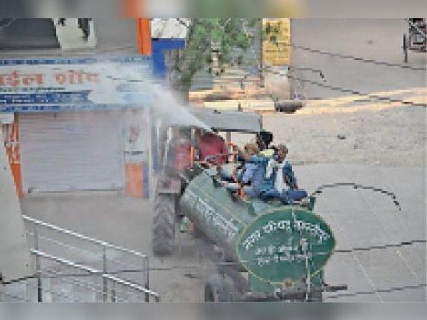 शहर के बाजार में पानी टंकी से सेनेटाइजेशन करता नप कर्मी। - Dainik Bhaskar
