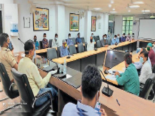 निजी अस्पताल संचालकों के साथ बैठक करते डीएम प्रणव कुमार, साथ में अन्य अधिकारी। - Dainik Bhaskar