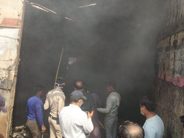 दुकान में लगी आग को बुझाने की मशक्कत करते हुए। - Dainik Bhaskar