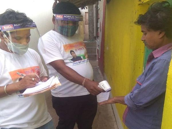 लोगों की जांच करने वाले इन लोगों ने महापौर की तस्वीर वाली टी शर्ट पहन रखी है।
