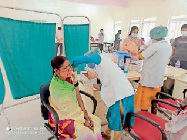 जीएनएम स्कूल में टीका लगवातीं महिला। - Dainik Bhaskar