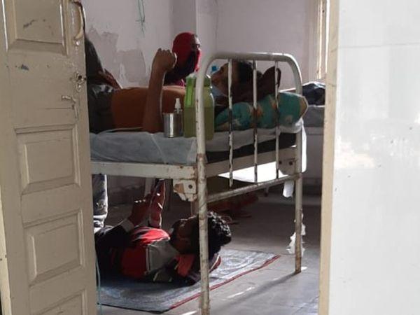 पलंग पर भर्ती कोरोना का मरीज और आइसोलेशन वार्ड में बेड के नीचे लेटकर मोबाइल चलाता अटेंडर। - Dainik Bhaskar