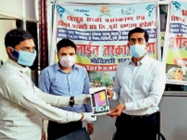 सब्जी बिक्री के लिए अधिकारी को टैब देते डीएम। - Dainik Bhaskar