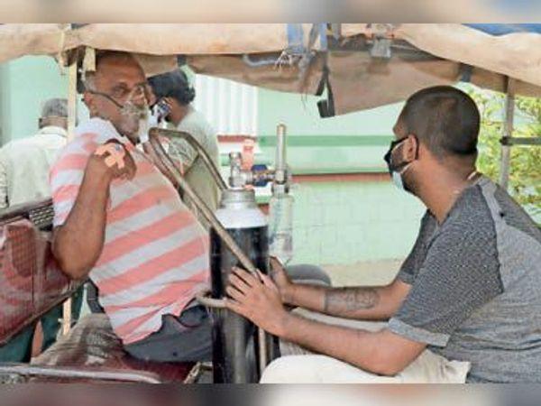 ई-रिक्सा पर बैठकर ऑक्सीजन के सहारे कोविड जांच कराने पहुंचे संदिग्ध मरीज। - Dainik Bhaskar