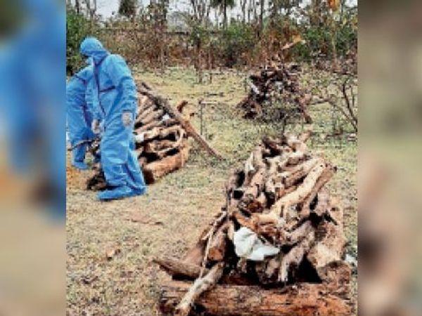 अंतिम संस्कार के लिए लकड़ी जमाते कर्मचारी। - Dainik Bhaskar