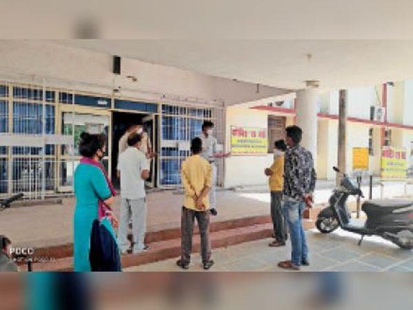 जिला अस्पताल के कोविड वार्ड में मरीजों की जानकारी उनके परिजनों को देते डॉक्टर एसएन शाक्य। - Dainik Bhaskar