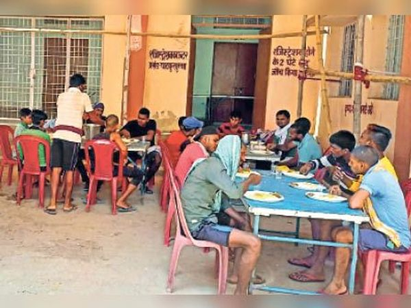 सामुदायिक किचन में भोजन खाते स्थानीय मुहल्लेवासी। - Dainik Bhaskar