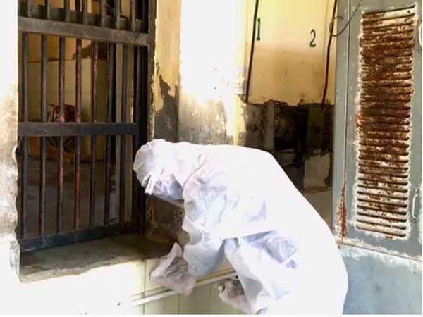 माचिया में शेरों के पिंजरे के बाहर सैनेटाइज करता एक कर्मचारी।