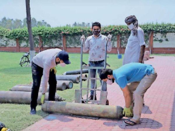 पानीपत. सिवाह स्थित राधा स्वामी सत्संग ब्यास केंद्र में जरुरतमंदाें काे ऑक्सीजन सिलेंडर रिफिल करवाकर देते हुए सेवादार। - Dainik Bhaskar
