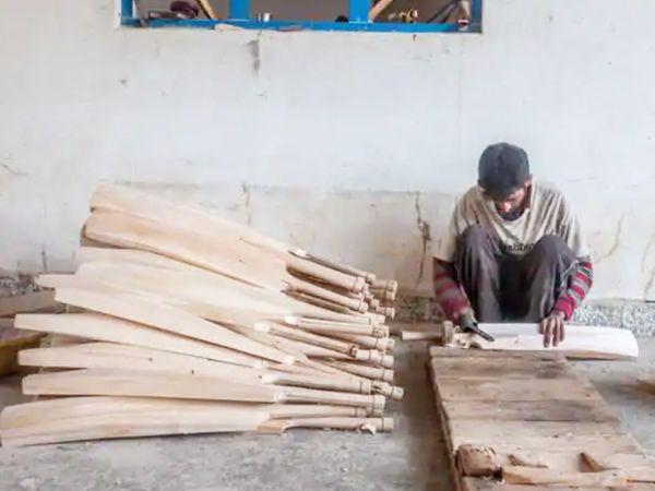 कश्मीर में बैट बनाता कारीगर।