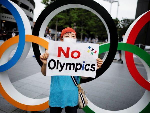 ओलिंपिक रिंग के सामने पोस्टर लेकर खड़ा शख्स।